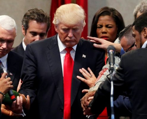 Members of the clergy lay hands and pray over Republican presidential nominee Donald Trump at the New Spirit Revival Center in Cleveland Heights, Ohio, U.S., September 21, 2016. REUTERS/Jonathan Ernst